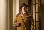 Photo du personnage se tenant droit : grand manteau orange-brun, chapeau brun, environ 50 ans, visage jovial mais pas trop, sacoche au bras.